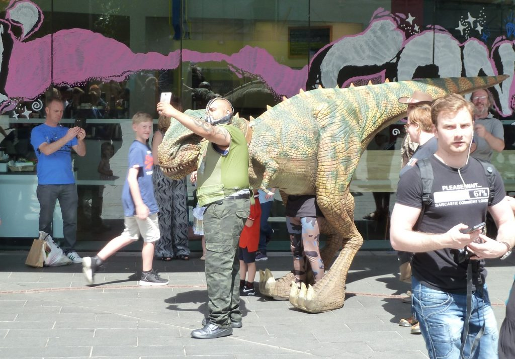 A dinosaur having it's photo taken by a masked man